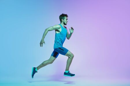 Portrait of active young caucasian man running, jogging on gradient studio background in neon light. Professional sportsman training in action and motion. Sport, wellness, activity, vitality concept.