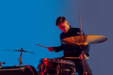 Caucasian male drummer improvising isolated on blue studio background in neon light. Performing, looks inspired, energy. Concept of human emotions, facial expression, ad, music, art, festival. Banque d'images