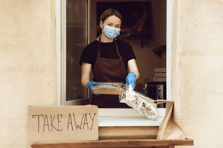 Fresh. Woman preparing drinks and meals, wearing protective face mask and gloves. Contactless delivery service during quarantine coronavirus pandemic. Take away concept. Recycable mugs, packages.