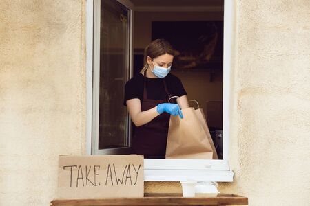 Healthcare. Woman preparing drinks and meals, wearing protective face mask and gloves. Contactless delivery service during quarantine coronavirus pandemic. Take away only concept. Recycable packages.