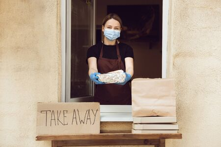 Be careful. Woman preparing drinks and meals, wearing protective face mask and gloves. Contactless delivery service during quarantine coronavirus pandemic. Take away only concept. Recycable packages.