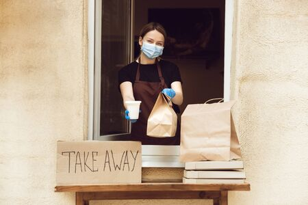 Safety. Woman preparing drinks and meals, wearing protective face mask and gloves. Contactless delivery service during quarantine coronavirus pandemic. Take away only concept. Recycable packages. Reklamní fotografie