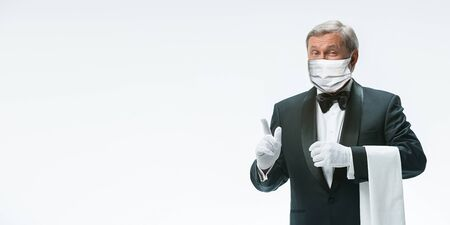Waits for you. Elegance senior man waiter in protective face mask on white background. Flyer, copyspace. Cafe, restaurant opening. Safety during coronavirus pandemic. Taking care of guests, clients.