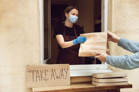Woman giving drinks and meals to client, wearing protective face mask and gloves. Contactless delivery service during quarantine coronavirus pandemic. Take away concept. Recycable mugs, packages.