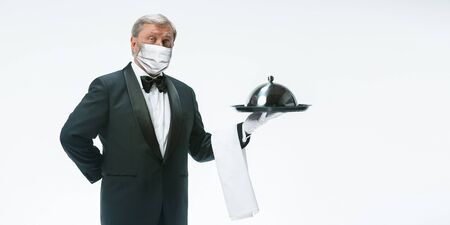 Emotional. Elegance senior man waiter in protective face mask on white background. Flyer with copyspace. Cafe, restaurant opening. Safety during coronavirus pandemic. Taking care of guests and clients.