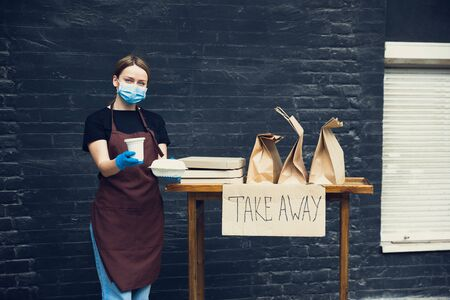 Protected. Woman preparing drinks and meals, wearing protective face mask and gloves. Contactless delivery service during quarantine coronavirus pandemic. Take away concept. Recycable mugs, packages.