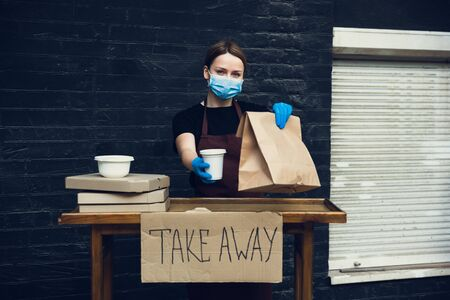 Choose health. Woman preparing drinks and meals, wearing protective face mask, gloves. Contactless delivery service during quarantine coronavirus pandemic. Take away concept. Recycable mugs, packages.