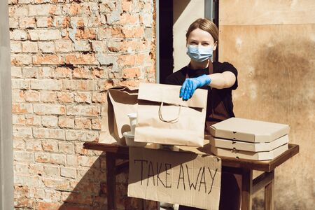 Lunch. Woman preparing drinks and meals, wearing protective face mask and gloves. Contactless delivery service during quarantine coronavirus pandemic. Take away concept. Recycable mugs, packages. Reklamní fotografie