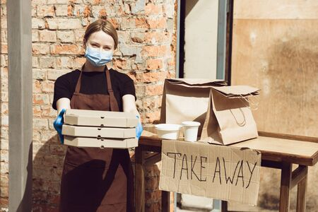 Pizza time. Woman preparing drinks and meals, wearing protective face mask and gloves. Contactless delivery service during quarantine coronavirus pandemic. Take away concept. Recycable mugs, packages.