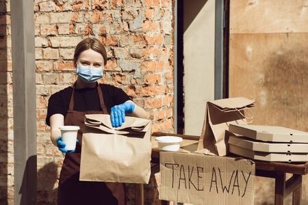 Burgers. Woman preparing drinks and meals, wearing protective face mask and gloves. Contactless delivery service during quarantine coronavirus pandemic. Take away concept. Recycable mugs, packages.