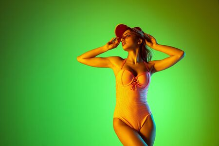 Sensual. Beautiful young girl portrait on gradient studio background in neon light. Woman in fashionable bodysuit and beach hat. Facial expression, summer, weekend, beauty, resort concept. Vacations. Фото со стока