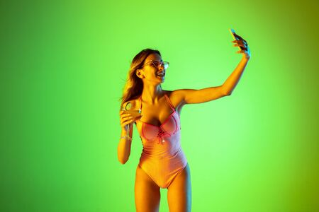 Selfie. Beautiful young girl portrait on gradient studio background in neon. Woman in fashionable bodysuit with cocktail. Facial expression, summer, weekend, beauty, resort concept. Vacations.