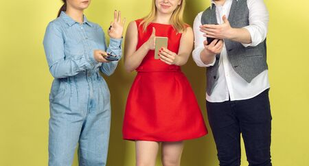 Group of friends using mobile smartphones. Teenagers addiction to new technology trends. Close up. Millenials texting, scrolling, chatting, watching video or shopping online. Connecting with devices.