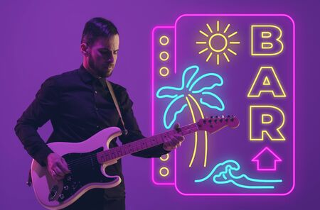 Young and joyful musician playing guitar on gradient studio background in neon light with sign BAR. Concept of music, hobby, festival. Colorful portrait of modern artist. Vacation, summertime, resort.