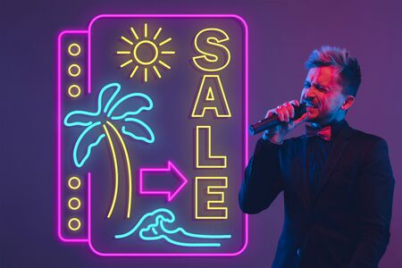 Young musician, party host singing on gradient studio background in neon with sign SALE. Concept of music, hobby, festival, summertime, vacation, resort. Stand upper. Colorful portrait of artist. Stockfoto