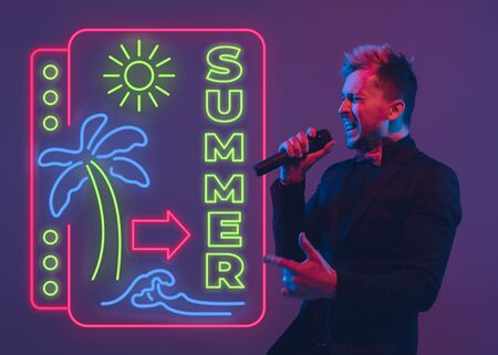 Young musician, party host singing on gradient studio background in neon with sign SUMMER. Concept of music, hobby, festival, summertime, vacation, resort. Stand upper. Colorful portrait of artist.