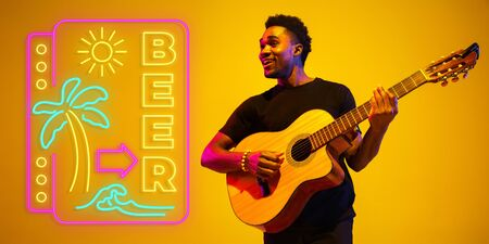 Young and joyful musician playing guitar on gradient studio background in neon light with sign BEER. Concept of music, hobby, festival. Colorful portrait of modern artist. Vacation, summertime, resort.