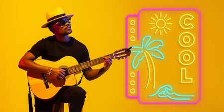 Young and joyful musician playing guitar on gradient studio background in neon light with sign COOL. Concept of music, hobby, festival. Colorful portrait of modern artist. Vacation, summertime, resort. Stockfoto