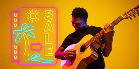 Young and joyful musician playing guitar on gradient studio background in neon light with sign SALE. Concept of music, hobby, festival. Colorful portrait of modern artist. Vacation, summertime, resort. Stockfoto
