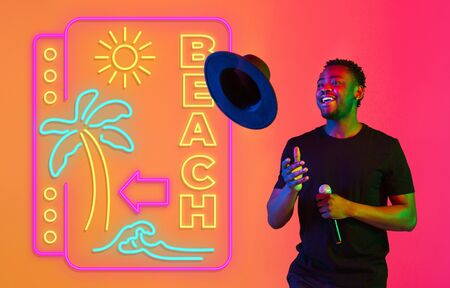 Young musician, party host singing on gradient studio background in neon with sign BEACH. Concept of music, hobby, festival, summertime, vacation, resort. Stand upper. Colorful portrait of artist.