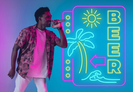 Young musician, party host singing on gradient studio background in neon with sign BEER. Concept of music, hobby, festival, summertime, vacation, resort. Stand upper. Colorful portrait of artist. Stockfoto
