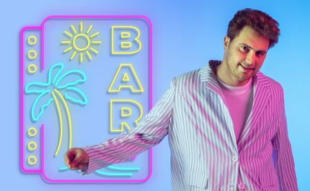 Young musician, party host singing on gradient studio background in neon with sign BAR. Concept of music, hobby, festival, summertime, vacation, resort. Stand upper. Colorful portrait of artist.