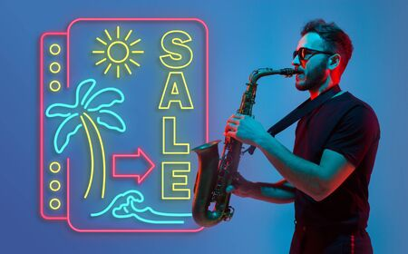 Young jazz musician playing the saxophone on gradient studio background in neon light neon sign SALE. Concept of music, hobby, festival. Joyful inspired artist, flyer. Summertime, sale, vacation.