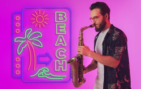 Young jazz musician playing the saxophone on gradient studio background in neon light with sign BEACH. Concept of music, hobby, festival. Joyful inspired artist, flyer. Summertime, sale, vacation.
