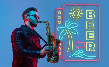 Young jazz musician playing the saxophone on gradient studio background in neon light neon sign BEER. Concept of music, hobby, festival. Joyful inspired artist, flyer. Summertime, sale, vacation. Stockfoto