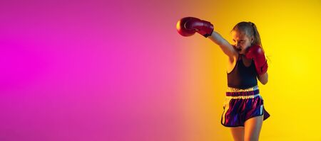 Little girl, kick boxer on gradient background in neon light, active and expressive. Concept of motion, action, motivation, childhood. Training winner, emotional. Sales, ad, flyer with copyspace.
