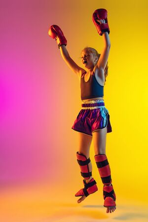 Little caucasian girl, kick boxer on gradient background in neon light, active and expressive. Concept of motion, action, motivation, childhood. Successful winner, emotional. Sales, ad, copyspace.