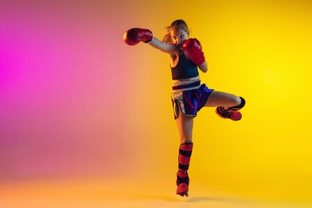 Little caucasian girl, kick boxer on gradient background in neon light, active and expressive. Concept of motion, action, motivation, childhood. Training winner, emotional. Sales, ad, copyspace.