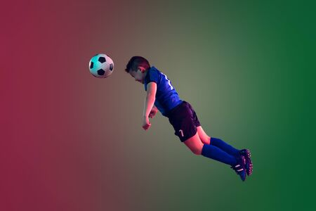 Teen male football or soccer player on gradient background in neon light. Caucasian expressive boy training, practicing on the run, in jump. Concept of sport, competition, winning, motion, action.