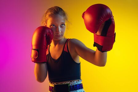 Close up little girl, kick boxer on gradient background in neon light, active and expressive. Concept of motion, action, motivation, childhood. Training winner, emotional. Sales, ad, copyspace.