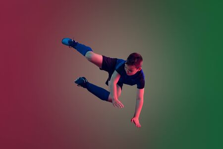 Unstoppable. Teen male football or soccer player on gradient background in neon light. Caucasian boy training, practicing on the run, in jump. Concept of sport, competition, winning, motion, action.