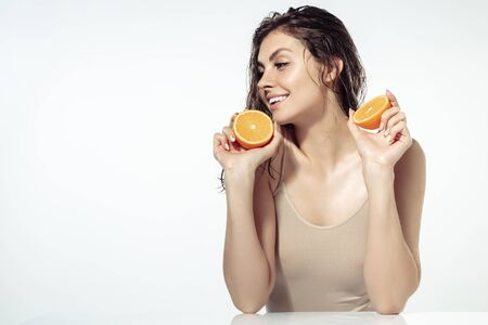 Juicy. Beautiful young woman with orange slices near face on white background. Concept of cosmetics, makeup, natural and eco treatment, skin care. Shiny and healthy skin, fashion, healthcare.