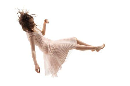 La belleza en el aire atrapó en el momento. Disparo de longitud completa de una atractiva joven flotando en el aire y manteniendo los ojos cerrados. Levitando en caída libre, falta de gravedad. Libertad, emociones, concepto de arte. Foto de archivo