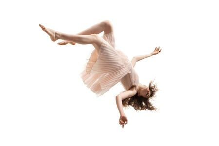 Mid-air beauty cought in moment. Full length shot of attractive young woman hovering in air and keeping eyes closed. Levitating in free falling, lack of gravity. Freedom, emotions, artwork concept. Foto de archivo