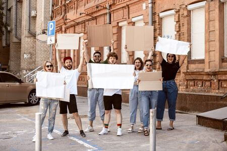 Diverse group of people protesting with blank sign. Protest against human rights, abuse of freedom, social issues, actual problems. Men and women on the street look angry, screaming. Copyspace. 版權商用圖片