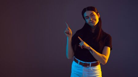 Pointing, choosing. Flyer. Caucasian young womans portrait on dark studio background in neon. Beautiful brunette model in casual. Concept of human emotions, facial expression, sales, ad. Copyspace.