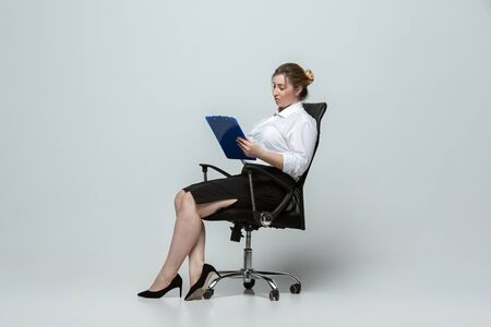 Meeting. Young woman in office attire. Bodypositive female character, feminism, loving herself, beauty concept. Plus size businesswoman on gray background. Boss, beautiful. Inclusion, diversity.
