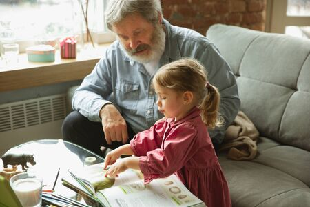 Grandfather and grandchild playing together at home. Happiness, family, relathionship, learning and education concept. Sincere emotions and childhood. Reading books, fairytails, poems, look happy.