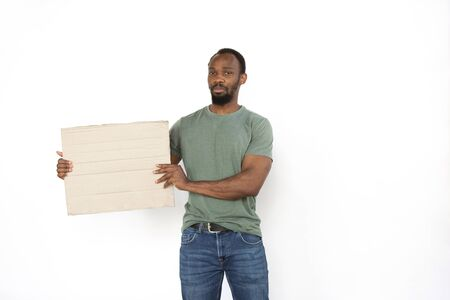 African man protesting with blank board, sign isolated on white studio background. Activism, active social position, protest, actual problems. Meeting against human rights, abusing, freedom of choice.