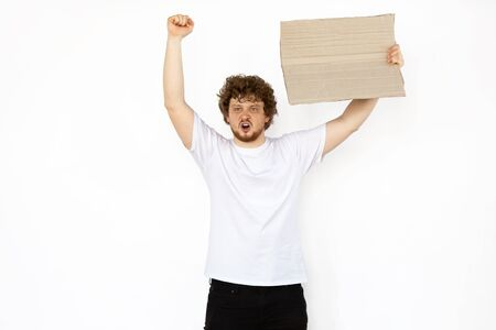 Young man protesting with blank board, sign isolated on white studio background. Activism, active social position, protest, actual problems. Meeting against human rights, abusing, freedom of choice.