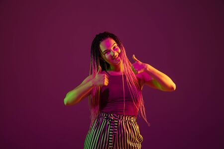 Young caucasian woman showing thumbs up on pink studio background in neon light. Beautiful model with dreadlocks. Human emotions, facial expression, sales, ad concept. Freaks culture. Copyspace.