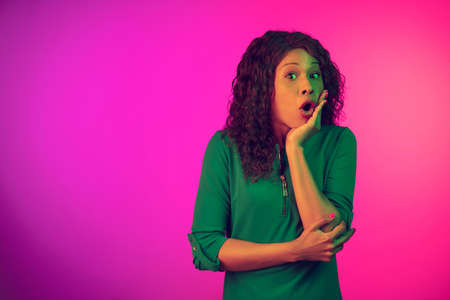 Shocked, interested. African-american young womans portrait on gradient pink background in neon light. Beautiful female model. Concept of human emotions, facial expression, sales, ad. Copyspace.