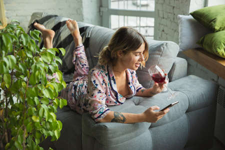 Drinking wine. Portrait of young girl in modern apartment in the morning. Calm, salisfied. Youth, wellness concept. Elegance woman in pajama spending time comfortable, scrolling phone. Looks cheerful.
