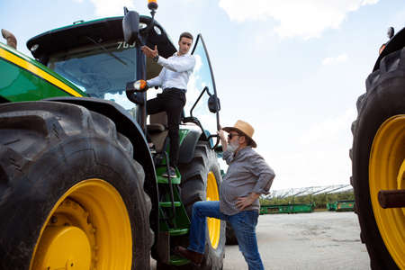Professional farmer with a modern tractor at work process. Looks confident, bright summer colors, sunshine. Agriculture, exhibition, machinery, plant production. Senior man with investor, buyer. Foto de archivo