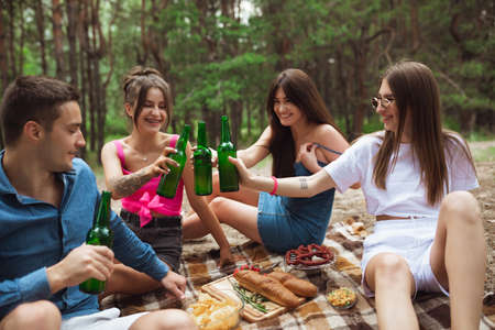 Happiness. Group of friends clinking beer bottles during picnic in summer forest. Lifestyle, friendship, having fun, weekend and resting concept. Looks cheerful, happy, celebrating, festive.