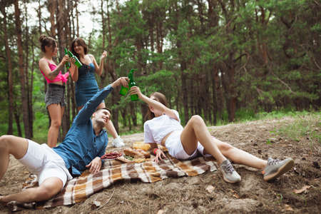 Togetherness. Group of friends clinking beer bottles during picnic in summer forest. Lifestyle, friendship, having fun, weekend and resting concept. Looks cheerful, happy, celebrating, festive.